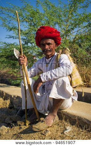 GODWAR REGION, INDIA - 14 FEBRUARY 2015: Elderly Rabari tribesman with red turban sits and holds ax and stick. Rabari or Rewari are an Indian community in the state of Gujarat.