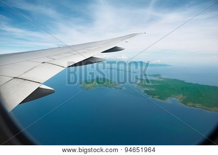Aerial View of jet plane wing on ocean and island