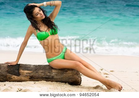 Young lady in bikini sunbathing on beach with azure sea in background