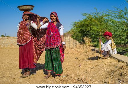 GODWAR REGION, INDIA - 14 FEBRUARY 2015: Rabari women stand in field wearing sarees and upper-arm bracelets with man sitting in background. Rabari are an Indian community in the state of Gujarat.