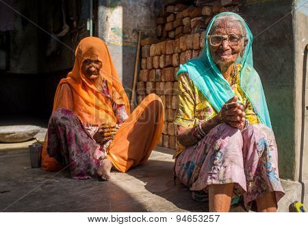 GODWAR REGION, INDIA - 13 FEBRUARY 2015: Two elderly Indian woman in sari's with covered heads sit in doorway of home.