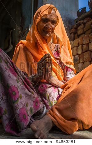 GODWAR REGION, INDIA - 13 FEBRUARY 2015: Elderly Indian woman in sari with covered head sits in doorway of home.
