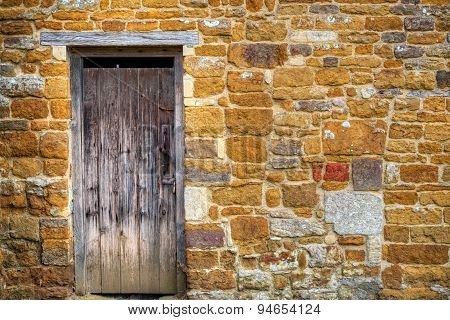 Old weathered wooden door in a stone wall