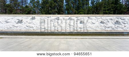Tianjin, China-May 22, 2015:dragon sculpture wall  with empty cement floor road in tianjin.