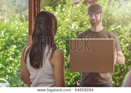 Woman Answering The Door To A Deliveryman