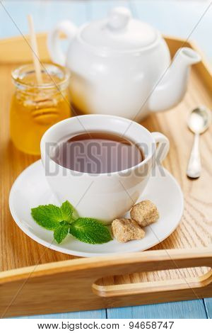 Cup of black tea with mint and honey