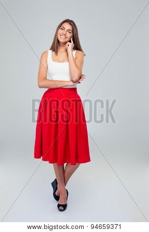 Full length portrait of a beautiful happy woman in skirt standing over gray background. Looking at camera