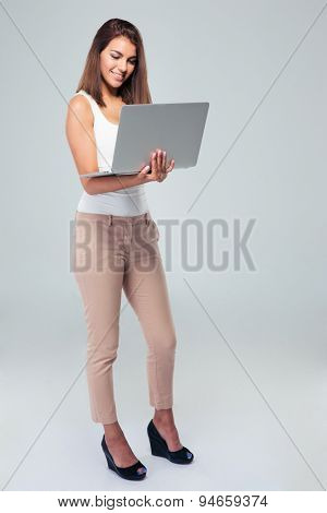 Full length portrait of a happy businesswoman using laptop over gray background