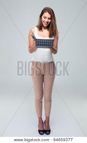 Full length portrait of a happy young woman opening gift box over gray background