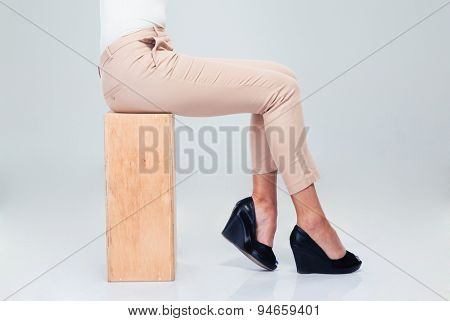 Closeup portrait of a woman sitting on wooden box over gray background