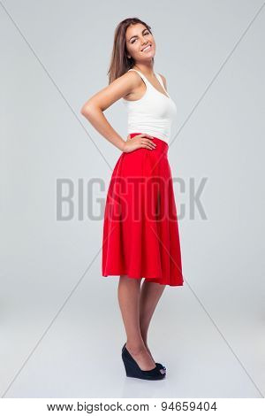 Portrait of a smiling pretty woman standing in skirt over gray background and looking at camera