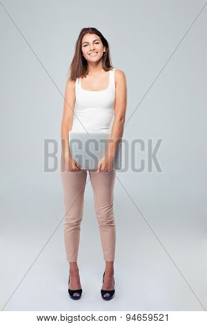 Full length portrait of a smiling woman holding laptop over gray backgorund