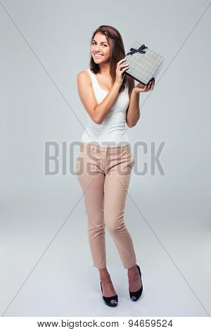 Full length portrait of a happy woman holding gift box over gray background. Looking at camera