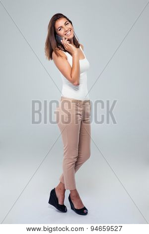 Full length portrait of a smiling woman talking on the phone over gray background. Looking at camera