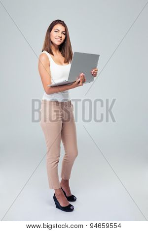 Full length portrait of a happy woman standing with laptop over gray background