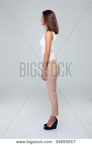 Side view portrait of a casual woman standing over gray background