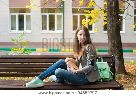 Student Sitting On Bench With Book