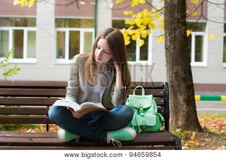 Student Reading Book In Autumn