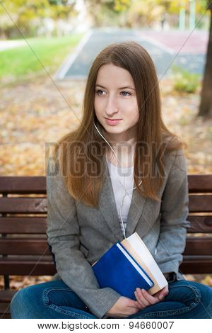 Student Sitting On Bench With Headphones And Book
