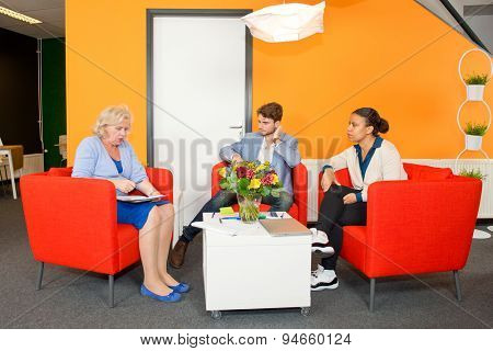 Small project team meeting in a stylish, modern lobby of an office building, between two young associates and a senior reintegrated woman.