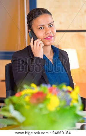 Young receptionist of a large cooperation taking calls on a phone