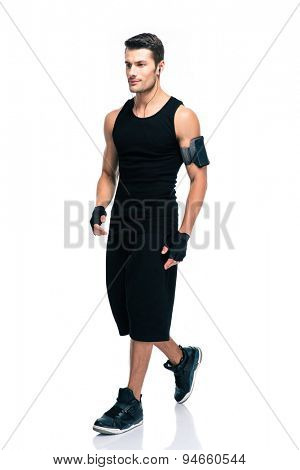 Full length portrait of a fitness man walking isolated on a white background. Looking away