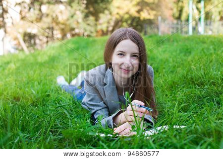 Student With Headphones Lying On Grass