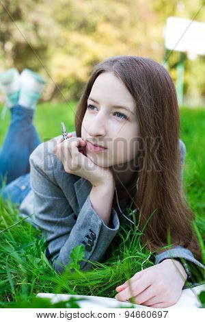 Student With Pen Thinking On Grass