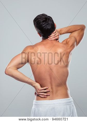 Back view portrait of a fitness man standing with back pain over gray background