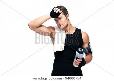 Tired fitness man with towel and bottle with water standing isolated on a white background. Looking at camera