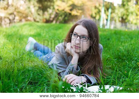 Student With Glasses Lying On Grass