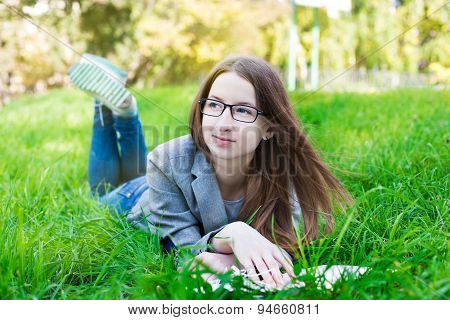 Student With Glasses Thinking On Grass