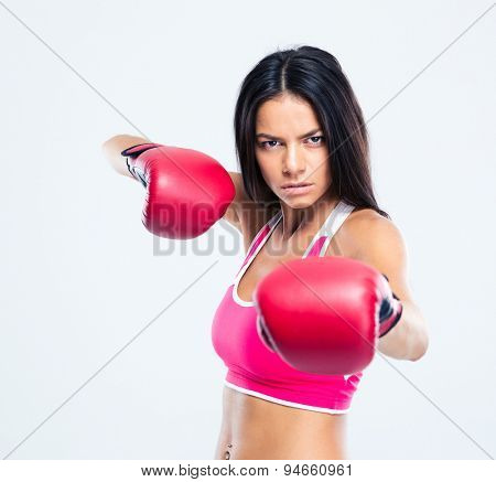 Portrait of a sporty woman with boxing gloves hitting at camera over gray background