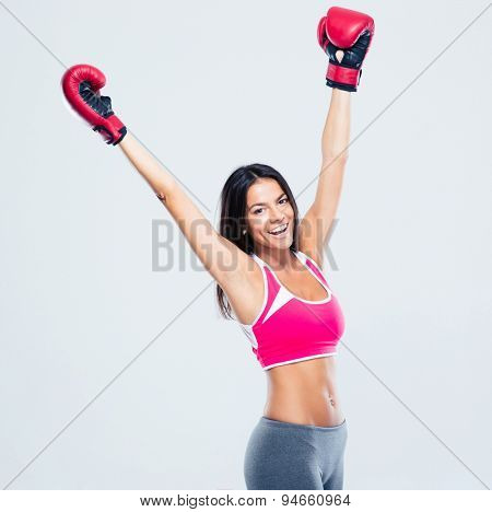 Cheerful sporty woman in boxing gloves celebrating her success over gray background