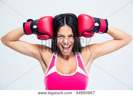 Fitness woman with boxing gloves screaming over gray background