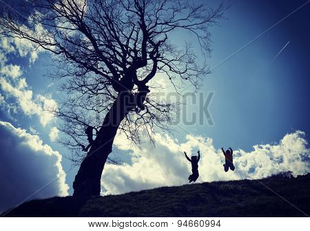 Silhouettes of happy children under tree on meadow