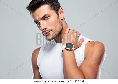 Portrait of a serious fitness man looking at camera over gray background