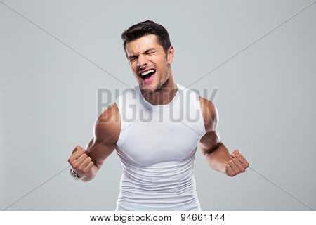 Muscular man celebrating his success over gray background