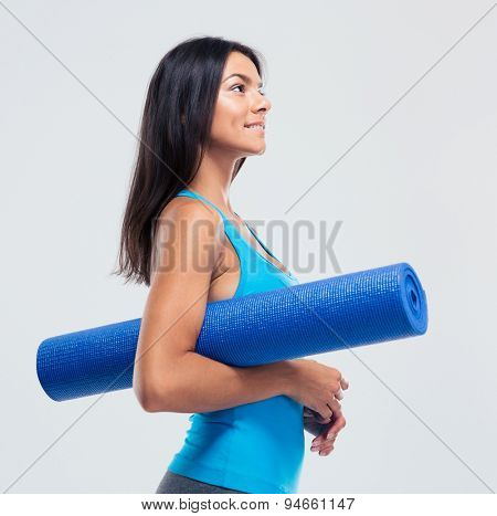 Happy sports woman holding yoga mat over gray background. Looking up