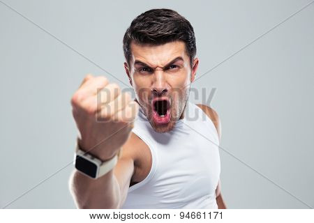 Angry man shouting and showing fist over gray background