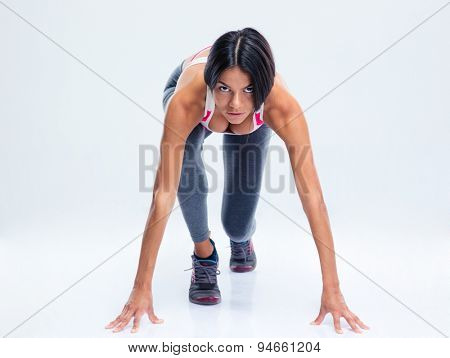 Runner sporty woman in start position over gray background. Looking at camera