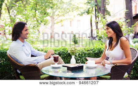 Young beautiful couple drinking coffee and having romantic time in outdoor cafe