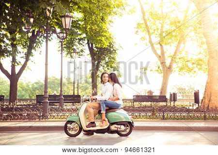Sideview of a trendy couple riding a scooter in the morning. Sun is shining through trees