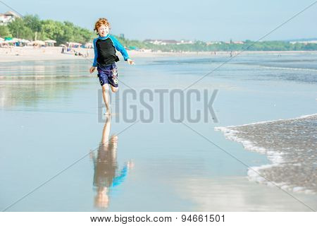 Young boy in swimming shorts and rash vest runs along Bali beach near sunset