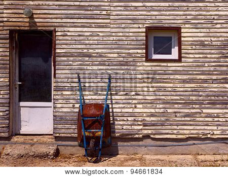 Rusty Old Wheelbarrow Leaning Against Wall