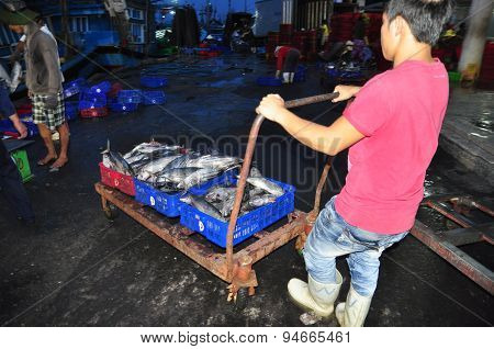 Nha Trang, Vietnam – February 21, 2013: Porters At The Hon Ro Seaport Are Loading Baskets Of Fishes