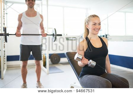 Young Fit Couple Lifting Barbells Inside The Gym