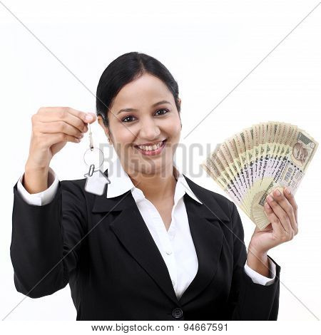Happy young business woman holding Indian currency and key