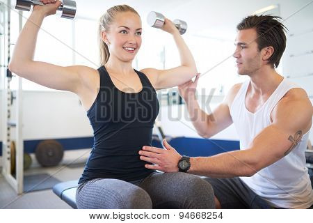 Gym Instructor Supporting Woman In Lifting Weights
