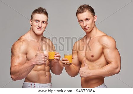 Two athletic men with glasses of orange juice